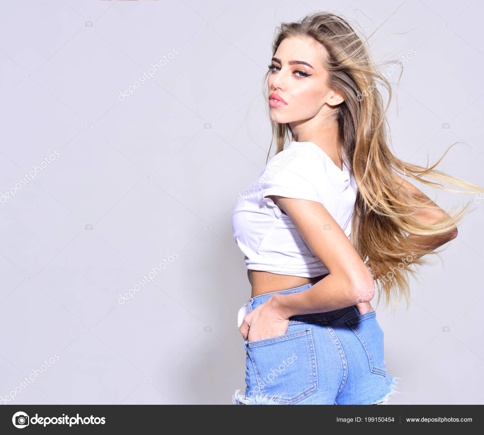 99f6805c2 Trendy girl with makeup on sensual face. Summer fashion for woman in summer  style. Sexy woman with stylish long hair in jeans shorts.