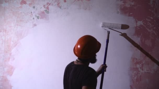 painter man at work takes the color with roller paint brush.