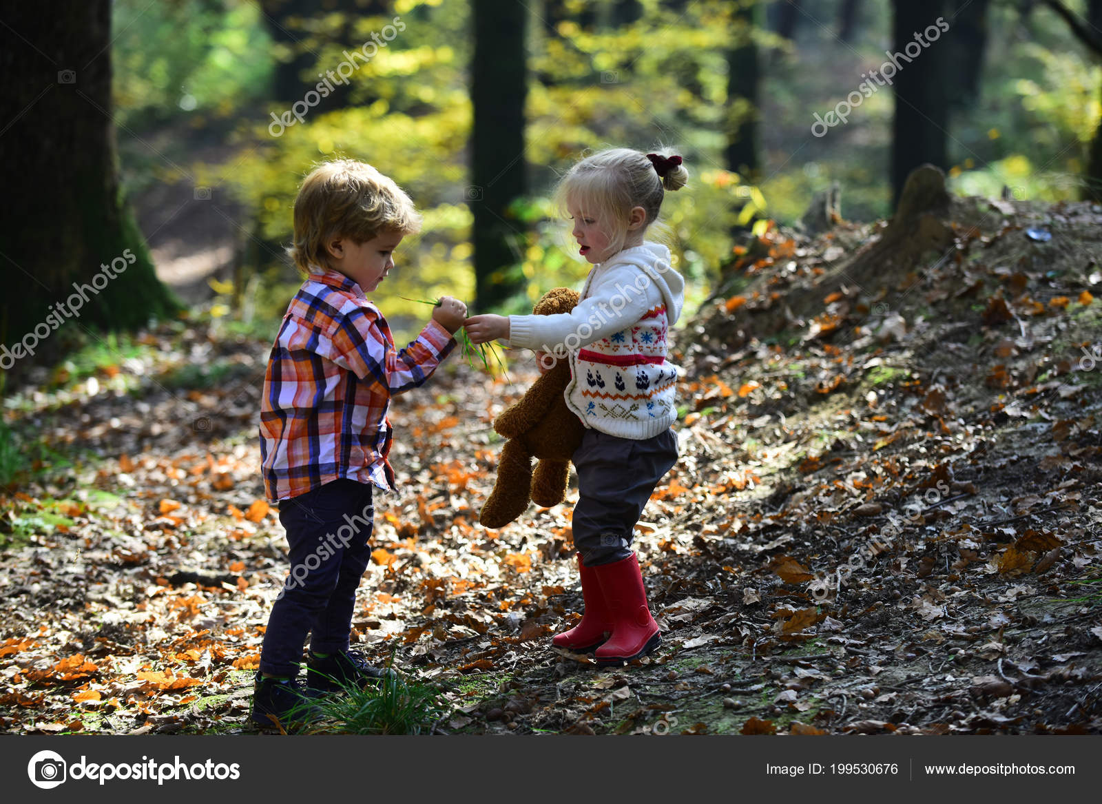 Kids Harvest Grass In Autumn Forest Brother And Sister Play On