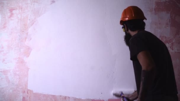 painter man at work takes the color with roller paint brush