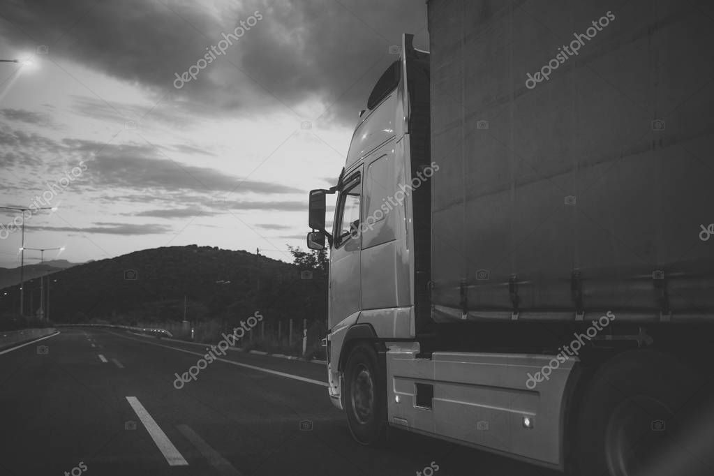 Camion, van rides along the road in evening, rear view. argo van, truck, kamion transports goods or items between countries. International transportation concept