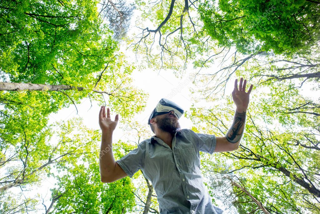 Man with beard in VR headset using digital touch screen. Bearded hipster in wireless goggles making gestures and exploring imaginary reality. Bearded man with tattooed arm testing gadget in forest