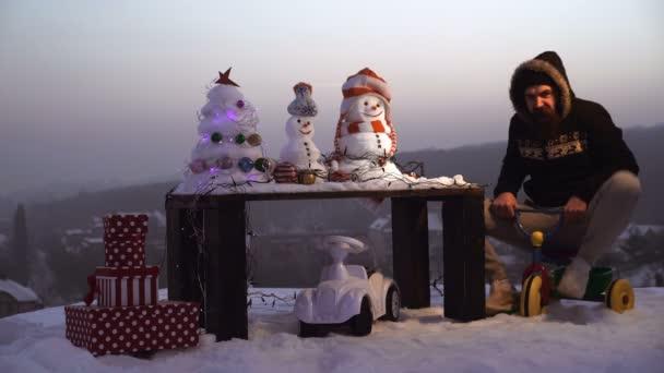 Boldog új évet a hóember. Snowmans boldog pár. Snowmans ünnepe. Izgatott férfi lovaglás tricikli szürke égbolt.