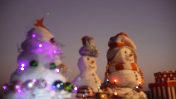 Nový rok. Sněhulák se uvolní dárky na nový rok. Uprostřed vánoční stromky na večer pozadí bílé sněhulák. Hračka dekorace. Selektivní fokus