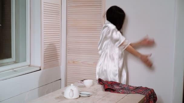 Junge hübsche Hausfrau in leichter Kleidung Tanz mit Familie Kleidung auf Bügelbrett mit Bügeleisen. Zimmermädchen-Konzept