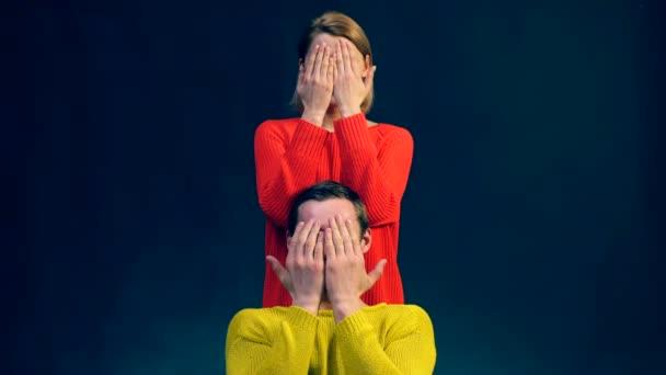 Dívka v červené barvě a chlapec v žluté svetry, objímala rukama ukazují různé emoce na černém pozadí. Emoce. Surprisment. Štěstí. Šok. Smutek