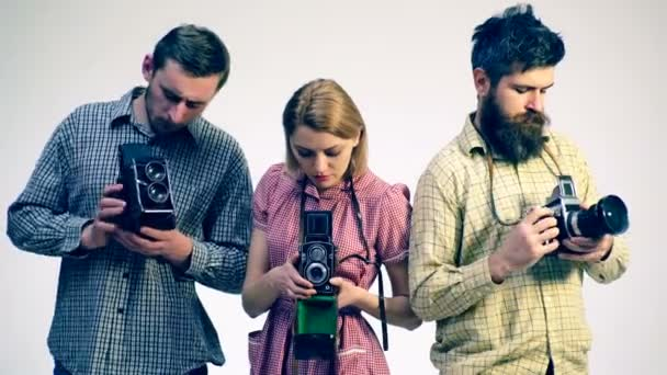 Three photographers are looking at old cameras. Photographers.