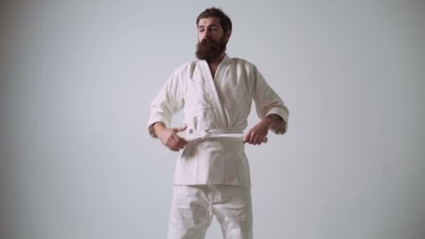 Vicces jóképű férfi egy képzeletbeli ellenfelet kényelmetlen ügyetlen elleni mozog. Vicces karate harcos fehér dzsúdóruhát visel