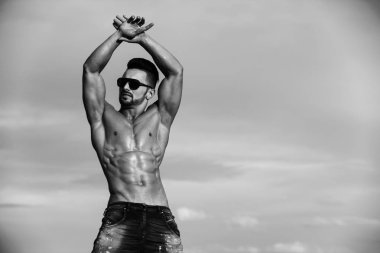 bodybuilder shows his body. guy with muscular body in sunglasses on blue sky