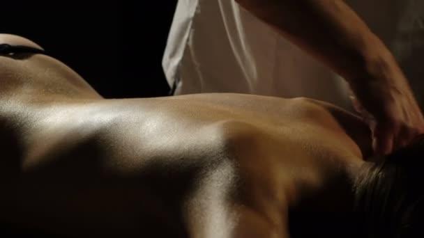 Ruce, které záda masáž close-up na černém pozadí. Relaxační masáž. Wellness hotel a lázně