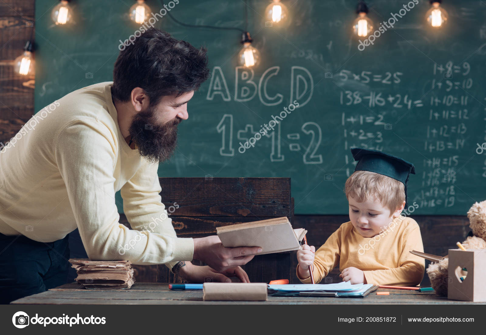Wunderkind And Genius Concept Father Teacher Reading Book Teaching Kid Son Chalkboard On Background Boy Child In Graduate