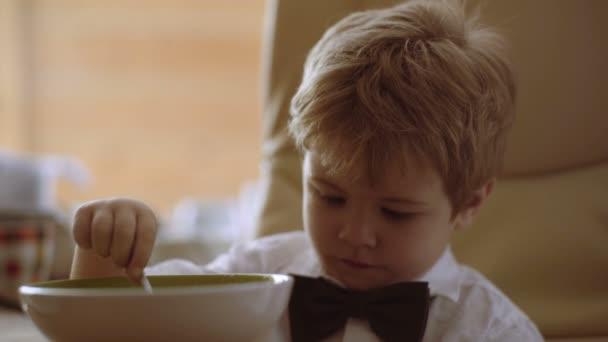 Šťastné dítě sledoval karikatury a jíst kaši. Veselé dítě sní jídlo, sám se lžičkou