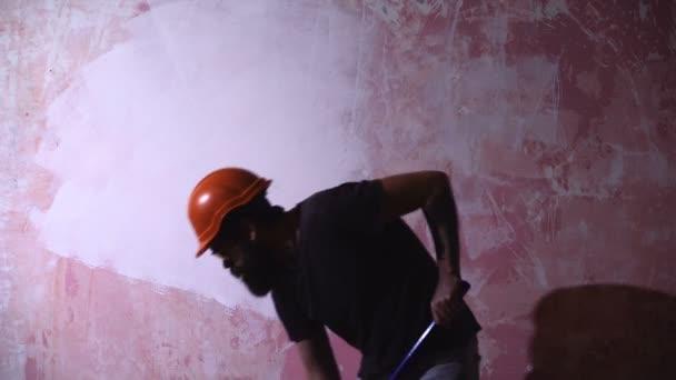 Muž Malování domu v Diy konceptu. Mladý muž na stěnu s válečkem