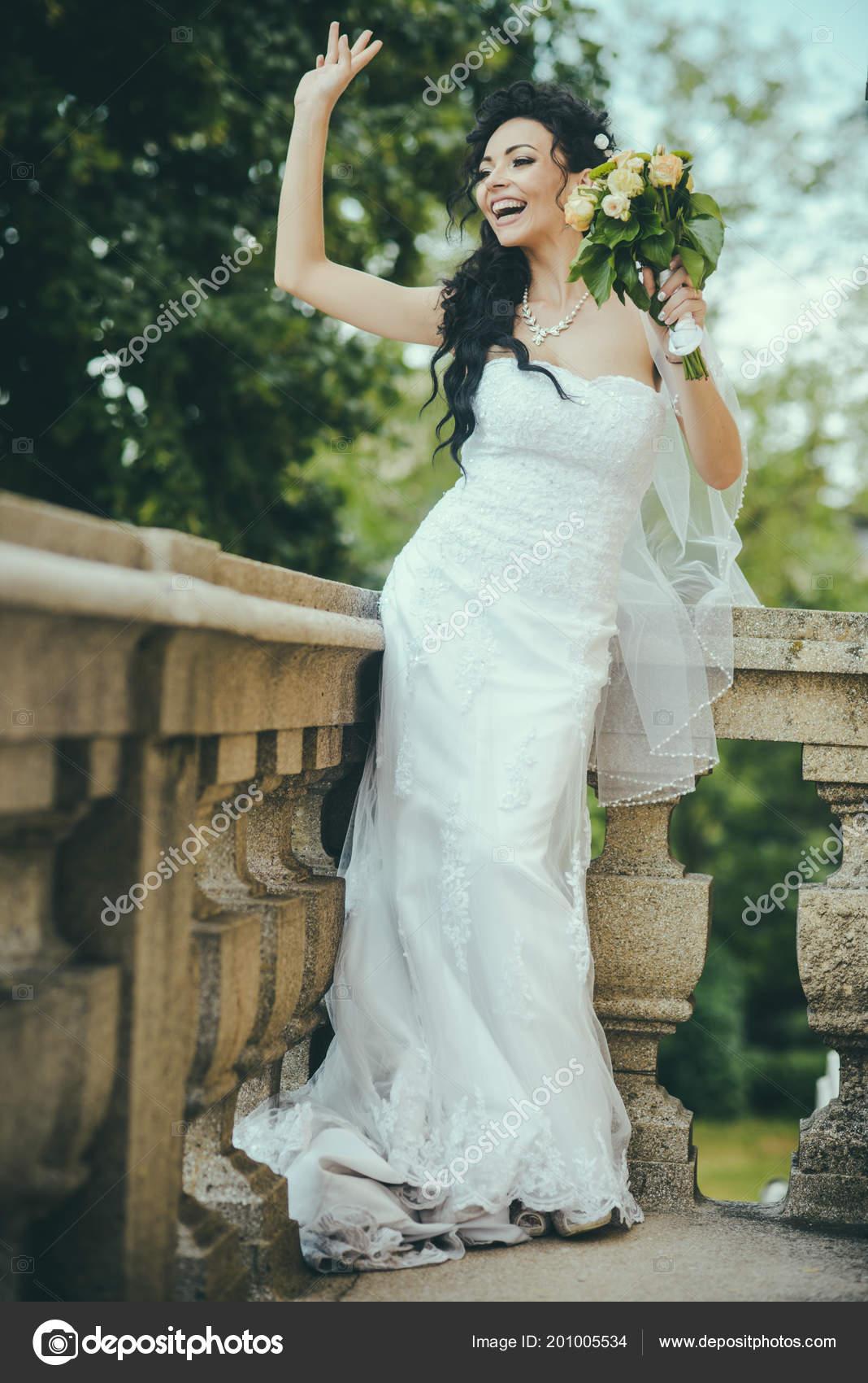 87ecdf915b88 Γυναίκα ομορφιά με γαμήλια ανθοδέσμη στο μπαλκόνι. Ομορφιά κορίτσι με το  νυφικό μακιγιάζ και χτένισμα σε λευκό φόρεμα– εικόνα αρχείου