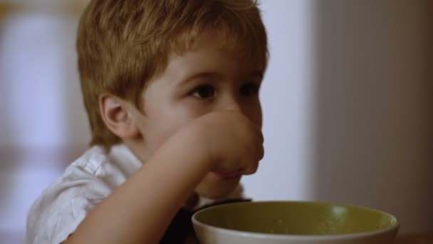 Dítě jí misku ovesné kaše k snídani. Dítě jíst zároveň sledovat kreslené filmy