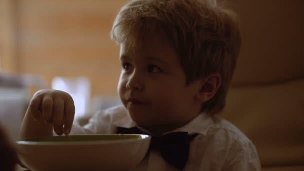 Dítě jíst zároveň sledovat kreslené filmy. Kluk jí misku ovesné kaše k snídani