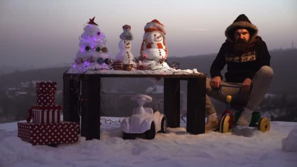 Šťastný nový rok s sněhulák. Snowmans šťastný pár. Snowmans oslava. Vzrušený muž jízda tříkolka na šedé obloze. Koncept oslav svátek