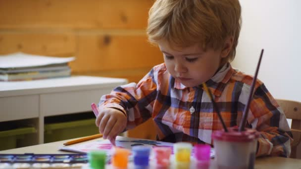 Kid Creativity Education Concept, Child Learning Art. Preschooler boy having fun with colorful paint at a daycare. Creative kid toddler drawing at home. Children play in kindergarten.