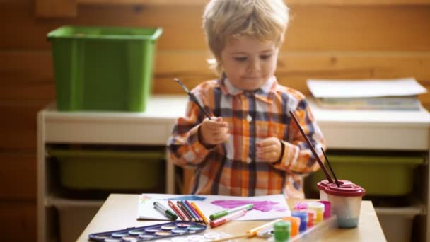 Kid Creativity Education Concept, Child Learning Art. Preschooler boy having fun with colorful paint at a daycare. Creative kid toddler drawing at home. Children play in kindergarten