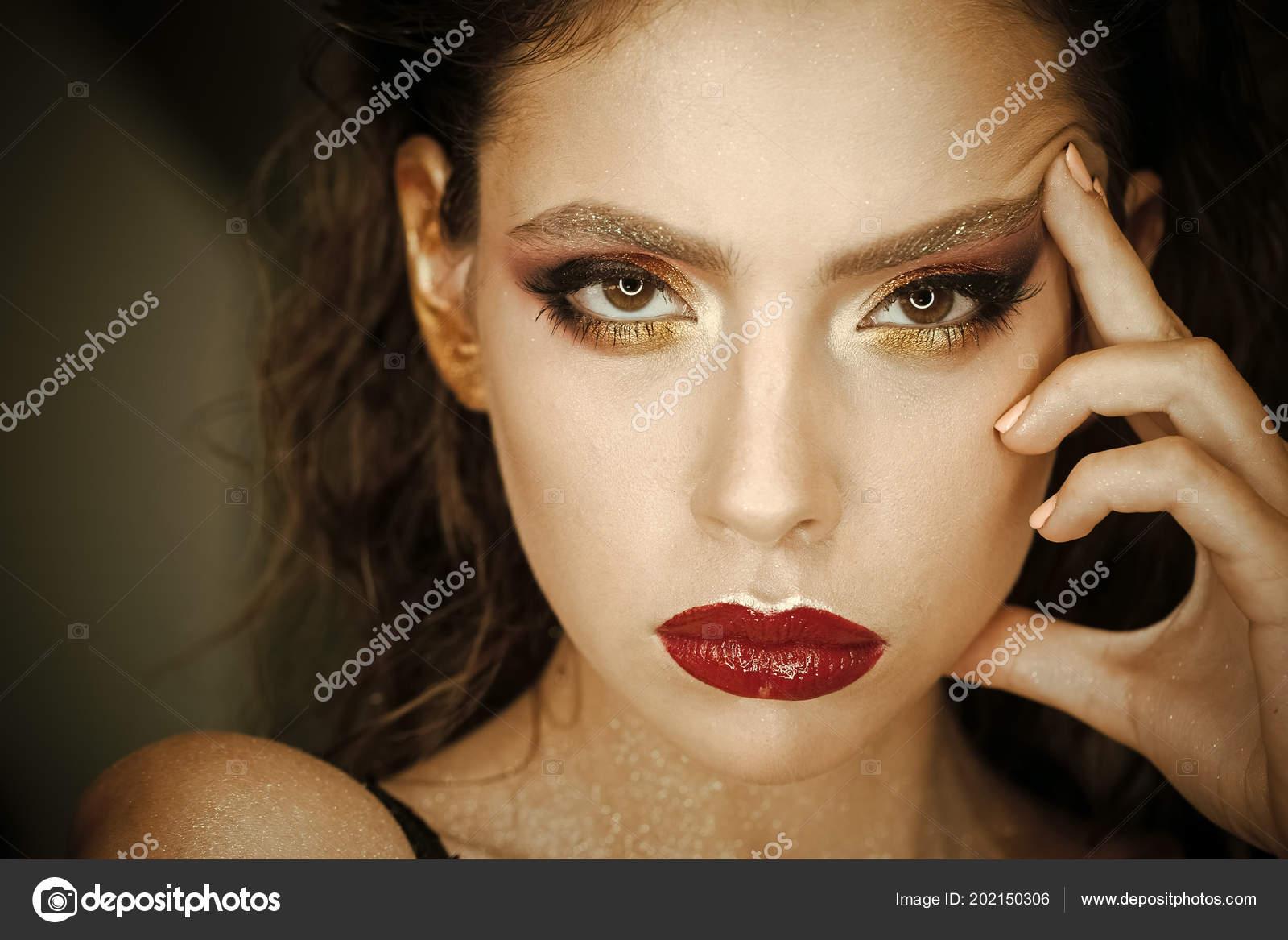 Trucco femmina. Donna alla moda che propone. Donna con pelle giovane viso,  cura della pelle. Donna con trucco luminoso e gli orli rossi, bellezza.