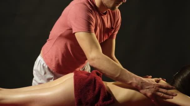 Masér provede masáž žena pokryté červený ručník na černém pozadí. Wellness a spa koncept.