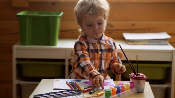 Cute little boy drawing in his album. Concept of early childhood education, painting, talent, happy family and parenting. Cute, serious and focused boy drawing.