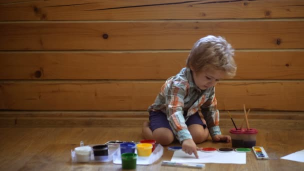 Psychology of the childs personality. Help gaining confidence. Drawing. Creativity and education concept. Happy cute boy colors his hands. Doing Finger painting. Art therapy for children