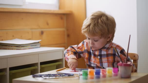 Happy cute boy colors his hands. Doing Finger painting. Art therapy for children. Psychology of the childs personality. Help gaining confidence. Drawing. Creativity and education concept