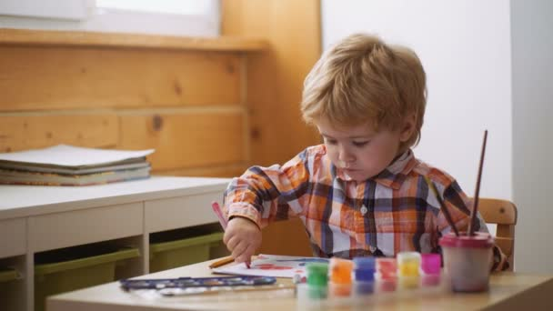 Child drawing picture with paitint in album using a lot of painting tools. Creativity concept