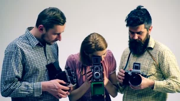 Concept of a photo case. Two guys and a girl in the process of creating a photo. Photographers are studying old cameras.
