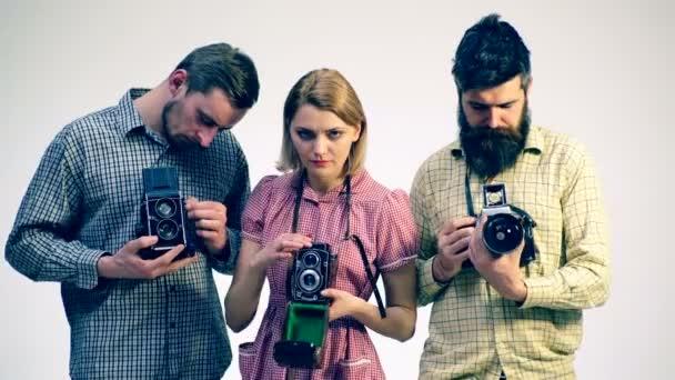 Drei Menschen mit Film-Foto-Kameras. Konzept der Studiofotografie. Antike Kameras