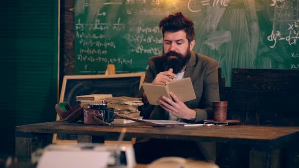 Profesor čte knihu, sedí u stolu v publiku. Koncept výuky. Školní děti v uniformě. Učitel v učebně. Učitel a student. Zpátky do školy