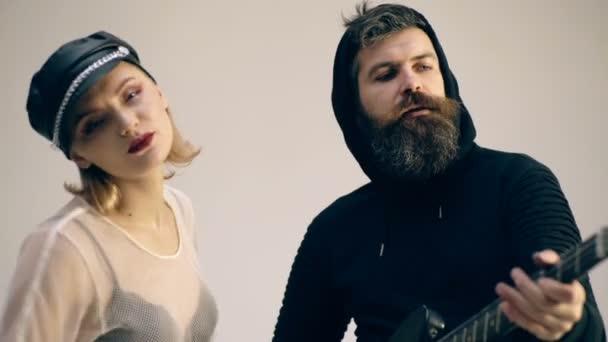 Rock pár énekelni és gitározni elszigetelt egy szürke háttér. Pár gitár cuddling szerelmes. Rock and roll concept.
