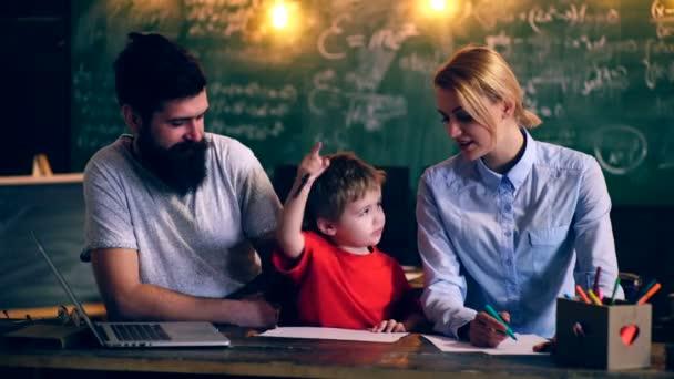 Dva učitelé učí chlapce školních osnov. Proces učení. Koncept výuky. Školní děti v uniformě. Učitel v učebně. Učitel a student. Zpátky do školy