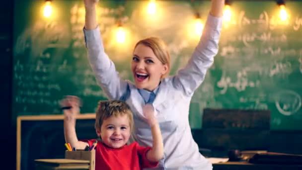 Chlapec s učitelem se raduje na jeho úspěch. Koncept výuky. Školní děti v uniformě. Učitel v učebně. Učitel a žák