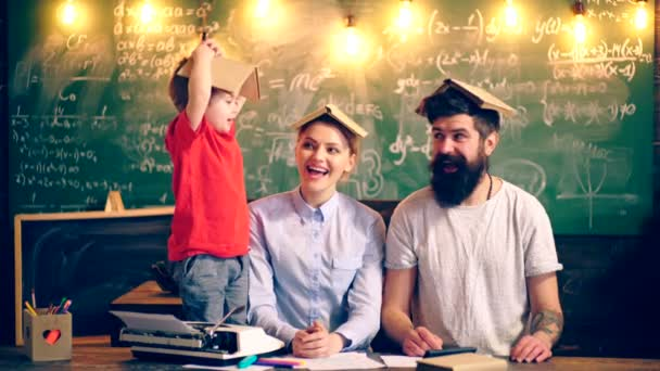 Two adults and a boy with books on the head are entertaining in the school class. Learning concept. Teacher in classroom. Teacher and student. Back to school.