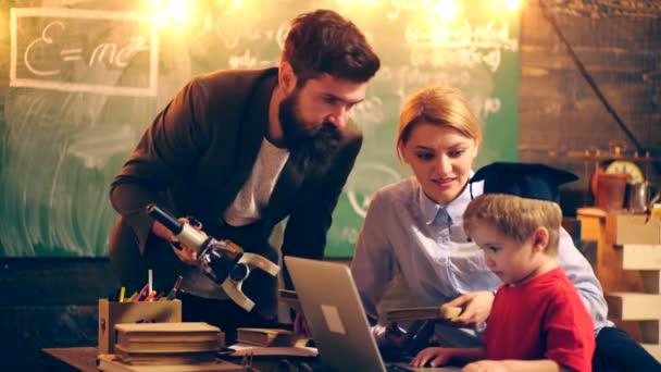 Két felnőtt tanárok az oktatási folyamat hozza a fiú. Tanulás-fogalom. Iskolás gyerekek egységes. Tanárnő az osztályban. Tanár és diák. Vissza az iskolába