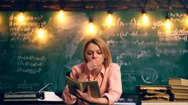 Žena čte knihu ve školní třídě. Koncept výuky. Školní děti v uniformě. Učitel ve třídě.