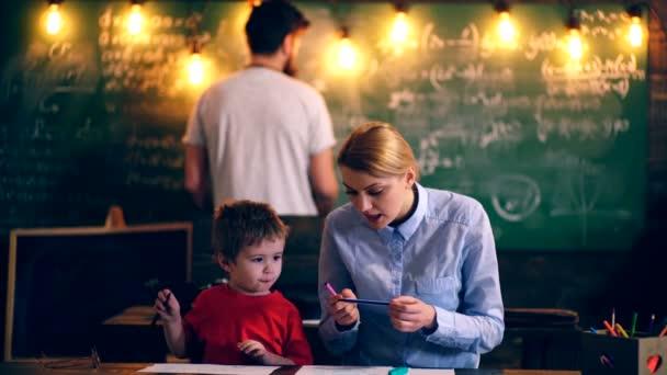 Ten kluk maluje v učebně s učitelem. Koncept výuky. Školní děti v uniformě. Učitel ve třídě