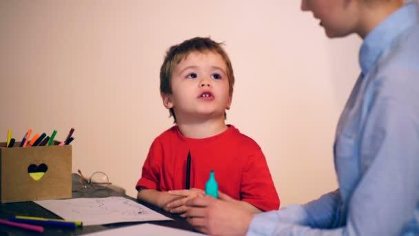 Chlapec se zabývá výkresu s učitelem na šedém pozadí. Koncept výuky. Školní děti v uniformě
