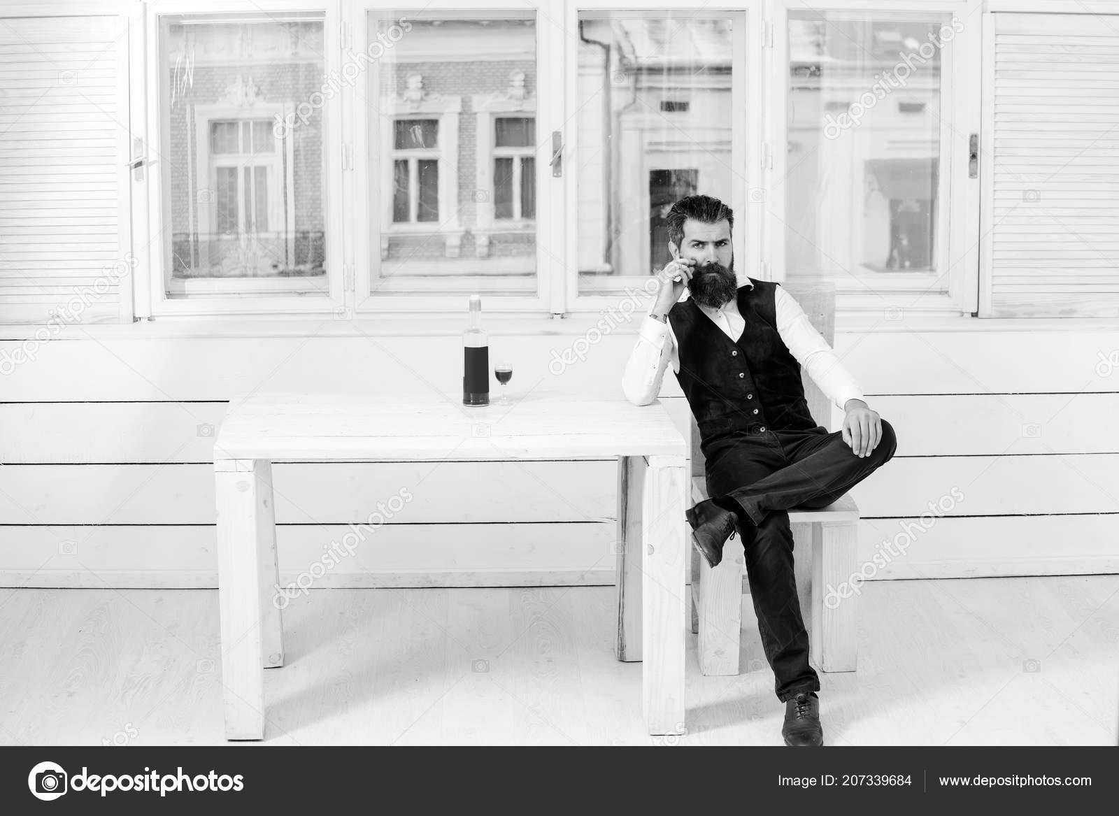 Wondrous Man Sitting On Chair At Table With Bottle And Glass Stock Frankydiablos Diy Chair Ideas Frankydiabloscom