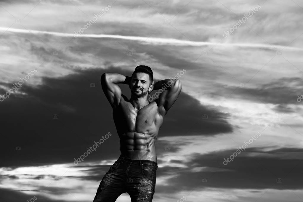 happy athlete man with muscular body on blue sky