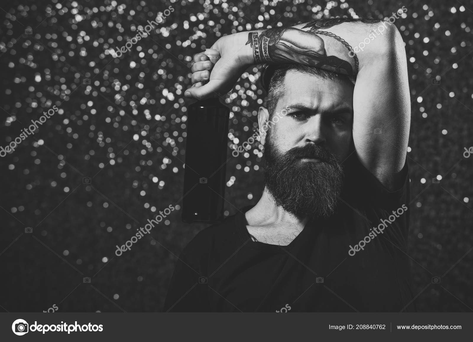 063222736 Mau hábito, dependência de álcool. Hipster com barba longa em tshirt preto  Segure o vinho. Tatuagem, moda, conceito de estilo.