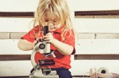 small baby boy with microscope and headset on wooden background