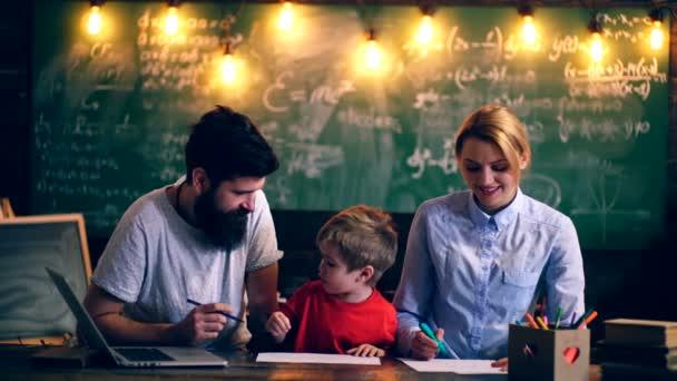 Otec, matka a jejich syn malovat ve školní třídě. Koncept výuky. Školní děti v uniformě. Učitel v učebně. Učitel a student. Zpátky do školy