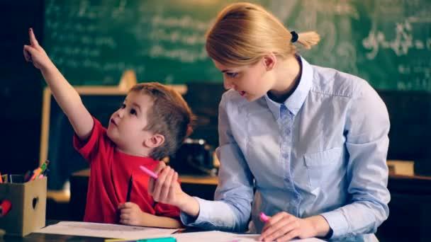 Učitel se zabývá školní třídy s mladým chlapcem. Školní děti v uniformě. Učitel v učebně. Učitel a student. Zpátky do školy