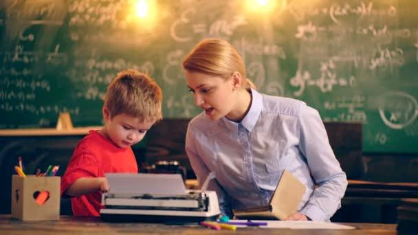 Chlapec s učitelem psaní na psacím stroji ve školní třídě na pozadí zelených Rady. Koncept výuky. Školní děti v uniformě. Učitel ve třídě