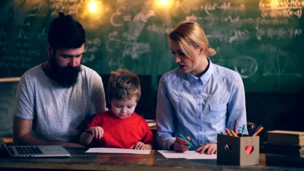 Rodiče učí chlapce kreslení v učebně školy. Lektoři vyučovat chlapce na pozadí zelené školní rady. Koncept výuky. Školní děti v uniformě