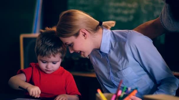 Otec a matka naučí syna nakreslit správně. Koncept výuky. Školní děti v uniformě. Učitel v učebně. Učitel a student. Zpátky do školy