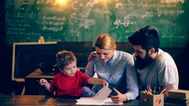 Chlapec a jeho rodiče čerpat v učebně školy na pozadí desky. Rodiče učí svého syna. Učitel a student. Zpátky do školy